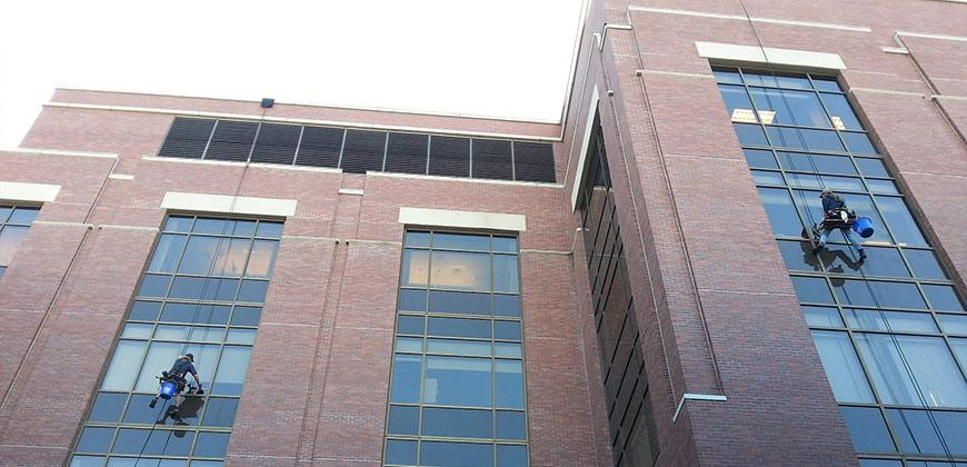 Zwei Fensterputzer putzen die Fenster einer Fassade