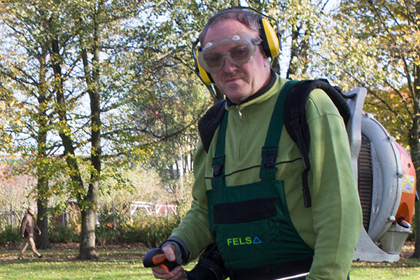 Hausmeister der Firma Fels-Services beseitigt Laub mit einem Rückenblasgerät.